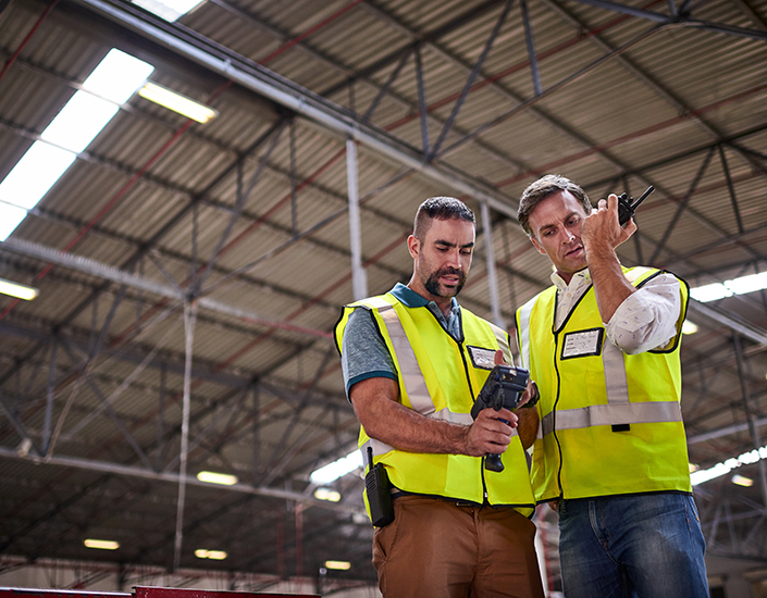 Low angle shot of two warehouse workers standing in a large warehouse